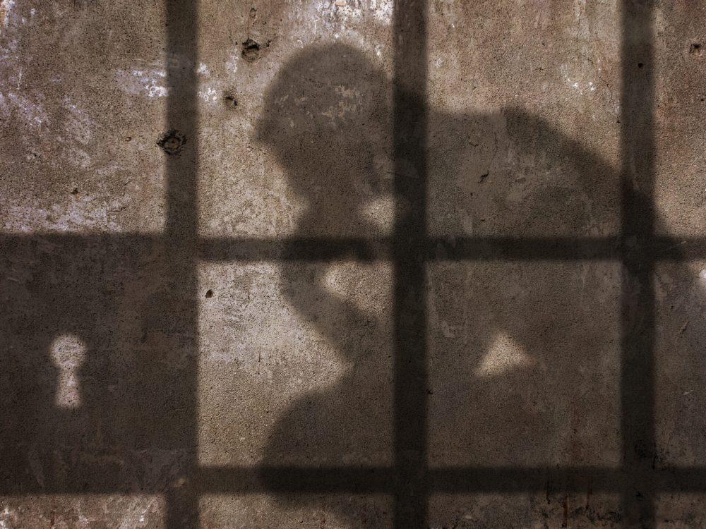Thinking,Man,Shadow,Under,Jail,Bars.